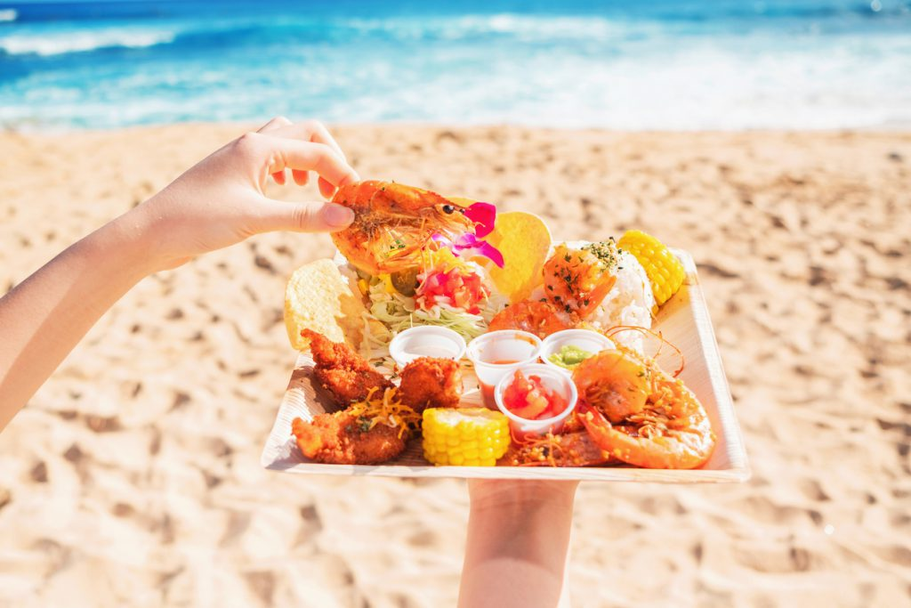Holding food plate of shrimp, rice, chicken, corn and sauces on the beach