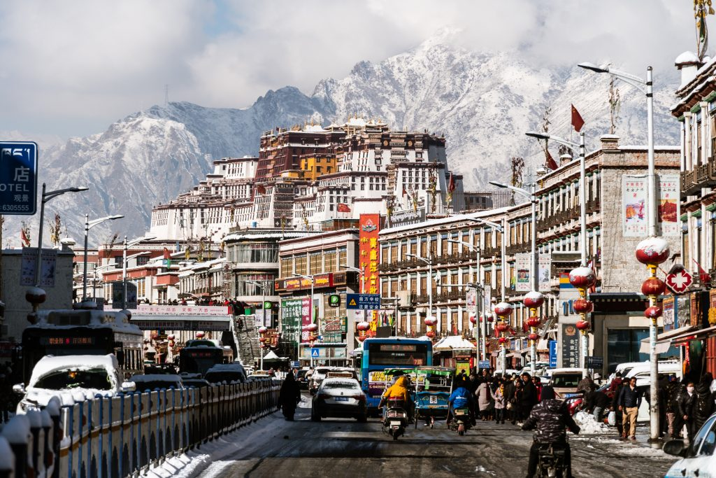 Traffic in the Lhasa old town with Potala Palace